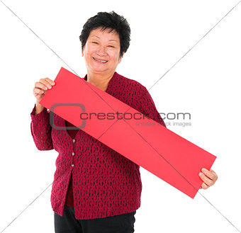 Chinese senior woman with red spring couplets