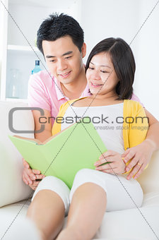 Asian couple reading book