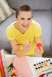 Smiling young woman drawing on Easter red egg