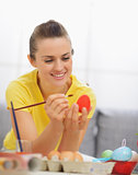 Happy young woman drawing on Easter red egg