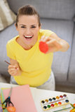 Smiling young woman showing Easter red egg