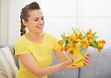Happy young woman with bouquet of tulips in bucket