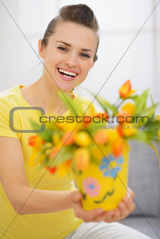 Happy young woman showing bouquet of tulips in bucket