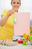 Closeup on blank pink paper sheet with Easter egg holding by wom