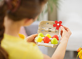 Woman making Easter decoration with colorful eggs