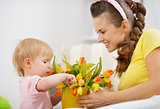 Happy mother and baby making decoration with bouquet of tulips i