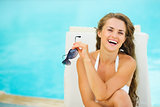 Portrait of happy young woman in swimsuit relaxing poolside