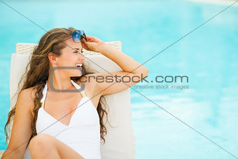 Happy young woman in swimsuit on chaise-longue and looking on co
