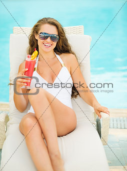 Happy young woman in swimsuit relaxing with cocktail on chaise-l