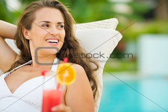 Smiling young woman in swimsuit with cocktail looking on copy sp