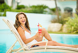 Smiling young woman in swimsuit relaxing with cocktail on chaise