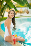 Smiling young woman sitting on pool edge with cocktail