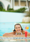 Happy young woman relaxing in pool with cocktail