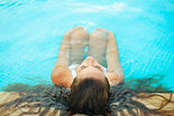 Woman relaxing in pool. Rear view