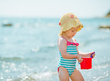 Baby playing with pail near sea