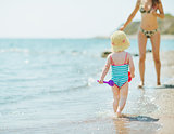 Baby running to mother along seashore
