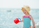 Smiling baby playing with pail on seashore