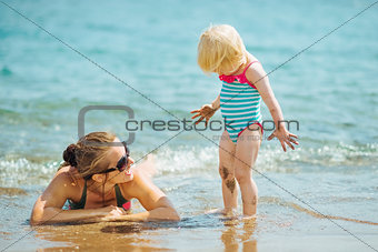 Mother and smeared with mud baby on sea beach