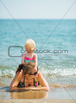 Baby playing with mother on seashore