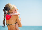 Baby hugging mother on sea beach