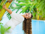 Laughing young woman leaning on tropical palm