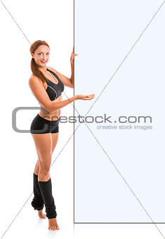 Fitness woman presenting empty billboard