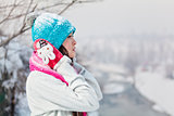 Girl in bright clouthes on snow winter background