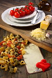 Cooking pasta with tomatoes and cheese.