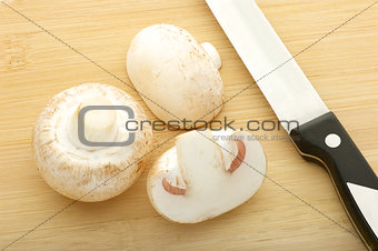 champignons and knife on bamboo cutting board