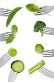 border of fresh green vegetables isolated on forks