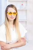 portrait of young woman with protective glasses in laboratory