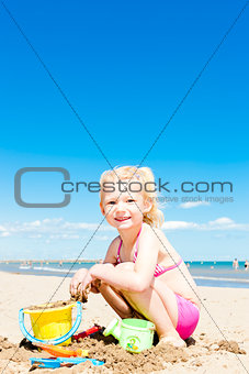 little girl playing on the beach at sea