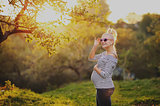 pregnant woman stands next to the sunset