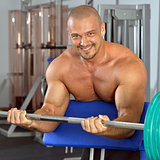 Strong man with naked torso exercising,  with barbell.