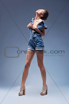 Attractive beauty girl in denim blue jeans overalls posing