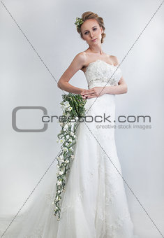 Sensual bride blond with floral bouquet of fresh tender flowers