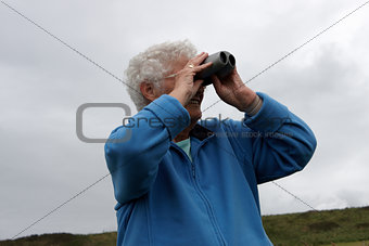 A senior lady using binoculars