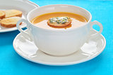 Close-up of roasted-pumpkin soup in a white bowl.