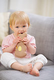 Baby eating Easter rabbit shaped cookie
