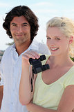 Couple using binoculars on a sunny day
