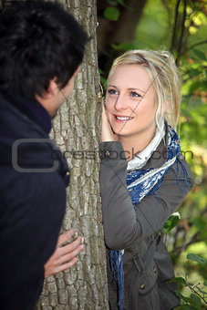 a blonde woman watching lovingly a man in the forest