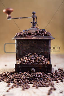 Old grinder with coffee beans