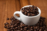 coffee beans and cup on wood surface