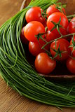 Fresh cherry tomatoes on wooden plate
