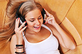 Relaxed woman listening to music in the living-room at home smil