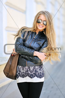 Portrait of young beautiful woman in sunglasses wearing black ja