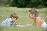 Mom helping son with homework, laying down on grass