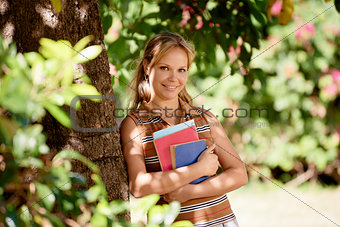 Student portrait at school, happy young woman with university bo