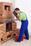 Worker installing door to a masonry heater