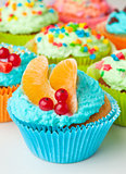 cupcakes with whipped cream decorated fruit and berries